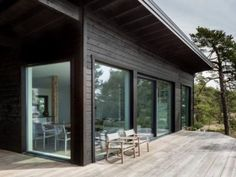 Dream Houses: Natural Eaves Of The House Deflect Wind And Keep The Temperature Inside Constant - Modern Scandinavian Log Cabin Set on a Beautiful Baltic Sea Island Black House Exterior, Exterior Doors, Modern Cottage, Baltic Sea, Cabins In The Woods, House And Home Magazine, Log Homes, Porches, Architecture Design