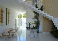 A sala para 3 ambientes integra um lounge próximo à entrada, decorado com lindas orquídeas que dão as boas-vindas aos moradores sobre uma mesa no foyer, e também as salas de estar e jantar.