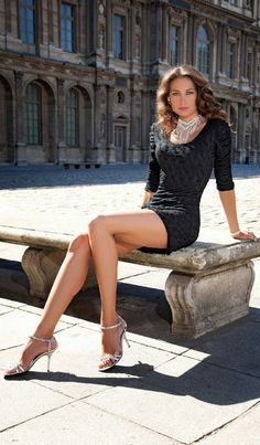 Long legged baroness in a mini dress and high heels sitting in front of her mansion