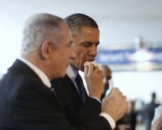 Obama and Israeli Prime Minister Benjamin Natanyahu trying matzo bread that was apparently served to them by miniature robots at a March 201...
