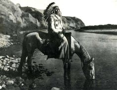 Blackfoot Chief at Bow River. By the late 1700's most tribes were mounted or had access to horses.  The horse, first introduced to the Blaclfoot in the 1730's greatly  improved their mobility.  The Blackfoot chief pictured here poses  proudly for Curts' camera in the beautiful setting of the Bow River.   Photographed by Edward S. Curtis in 1910. I love this photo, as old as  it is you can see the ripples and the reflection of the horse in the  water.