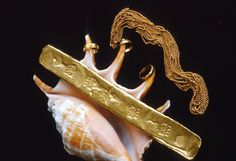Caption 30- A Colombian gold bar of 20.75 kt struck at the Peña-Randa foundry 1621-22. A heavy gold chain and delicate gold rings attached to the fingers of a conch shell. -Recovered from the Florida Keys wreck site of Nuestra Señora de Atocha - 1622.