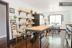 Open shelving and hooks for hanging cookware under the butcher block table were clever alternatives to cabinets in a rehabbed vintage kitchen in Austin.
