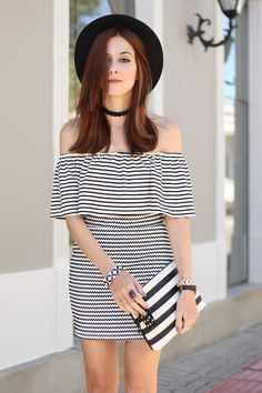 Black and white classic striped outfit wearing a gorgeous off the shoulder ruffle top and skirt. Also wearing classic hat and white heels.