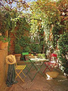 Patio con pequeña mesa de hierro y sillas de colores rodeado de naturaleza