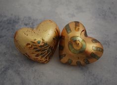 Pair of Heart in Hand Rattles by Valerie Seaberg. These porcelain rattles are finished with an application of gold leaf. Sold in a pair as shown.