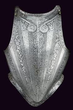 An engraved breast-plate dating: late 16th Century provenance: North Italy made of iron, slightly protruding neckline, smooth gussets; small defects; the entire surface engraved with bands in the Pisan manner, at the upper part two medallions depicting busts over an oval cartouche featuring a human figure; the bands decorated with armour parts, animals and floral motifs.