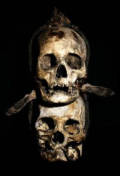 IFUGAO TRIBE: TWO HUMAN TROPHY SKULLS  HUMAN SKULLS, RATTAN, AND TWO ANIMAL FEET.  THE IFUGAO TRIBE, FROM THE PHILIPPINES, PLACE HEAD HUNTED  HUMAN TROPHY SKULLS OUTSIDE OF THEIR HUTS, AS WELL AS,   MOUNT THEM OVER THEIR HEARTHS INSIDE OF THEIR HOMES.