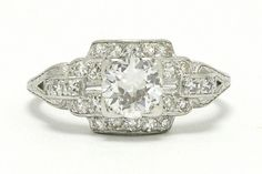 The Anaheim Art Deco diamond engagement ring. The bold, geometric platinum setting highlighting a 3/4 carat old European brilliant that explodes with a rainbow of sparkle. Completing this 1920s Jazz Age design is a surround of diamonds terminated by a crisply-engraved buckle motif band. Perfect for everyday wear as she rides nice and low on your finger. #artdeco #diamond #engagementring #platinum #heirloomring #heirloomjewelry #heirloom #artdecoring #artdecorings #diamondring #diamondrings… Estate Engagement Ring, Antique Engagement Rings, Diamond Engagement Rings, Art Deco Ring, Art Deco Diamond, 1920s Jazz, Heirloom Rings, Jazz Age, Diamond Rings