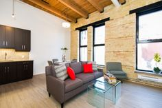 The LOMBARD at District Condos - Loft style conversion condos featuring exposed brick, century old wood beams, 14 ft ceilings and modern finishes. Saarinen table, modern grey chairs. Mini mosaic backsplash