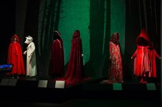 "Clothing illustrating ""Little Red Riding Hood."" From left to right: 18th-century cloak, 19th-century nightgown, 1970s cloak by Giorgio di Sant'Angelo, cloak by Altuzarra, dress by Dolce and Gabbana, ensemble by Comme des Garçons. Chanel No. 5 video courtesy of Chanel. Photograph © 2016 The Museum at FIT."