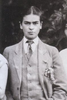 In this close-up from a family portrait, a young Frida experiments with androgynous style, flouting traditional norms by donning a gentleman's suit and slicking back her hair. Frida the rebel.