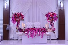 Gorgeous, breathtaking bride and groom head table with hanging orchids and candles.  Purple and pink flowers.  Elegant and romantic.