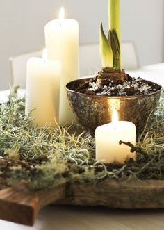 Vintage silver, candles, and moss on an antique cutting board.