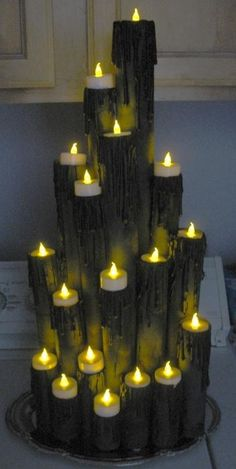 Wrapping paper tube, paper towel tubes and TP tubes. Hot glue, flat black spray paint and LED tea lights. Pretty cool and no fire danger.