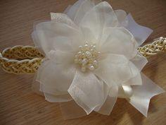 Faixa trançada em perolas douradas, flor em camadas bordada com mini perolas sobrepostas.  Ajuste com elastico macio e confortavel na nuca.  disponvel tambem na cor branca.  Informe a idade da sua princesinha.