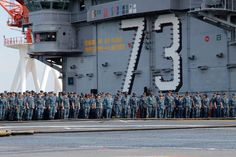 (May 31, 2013) The crew of the U.S. Navy's forward-deployed aircraft carrier USS George Washington (CVN 73) stands at attention on the ship's flight deck during morning colors before an all hands frocking ceremony.