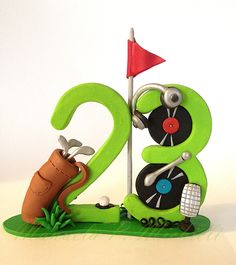 Polymer Clay cake topper celebrating a 23 years old man who loves playing golf and DJing - by Manuela P. Michieli