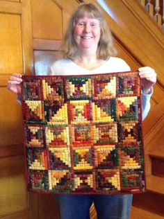 """Fall-colored batik Log Cabin quilt, designed and pieced from 1/2""""-wide logs by my good friend, Chris Hulin, 2014. Hand quilted by Judy Martin. Chris made 4.5"""" blocks using three values, several block colorings, and both Courthouse Steps and regular Log Cabin construction. She made it as a gift to me, and I am overwhelmed. Wow! --Judy Martin"""