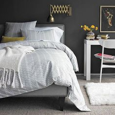 Love the dark gray walls, pops of yellow and gold and the desk serving double time as a nightstand.