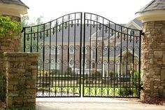 WOW! This is spectacular! The round stone columns are oozing with charm and character - capped off and shingled. The iron gate is a thing of beauty. Love