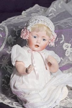 """GERMAN BISQUE """"HILDA"""" BABY BY KESTNER. Marks; F made in Germany 10, 237 JDK © Hilda. 13"""". Bisque socket head, blue sleep eyes, painted lashes, feathered brows, open mouth, shaded and accented lips, two upper teeth, blonde mohair wig, composition bent-limb baby body, white cotton gown, crocheted bonnet. Commentary: Sweet-faced little character with fine quality bisque and decoration, excellent original body with original finish; upper right eye rim repair."""
