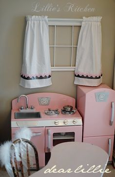 What a cute idea to put a fake window and curtains above the play kitchen. Thinking of doing this in the cubby house