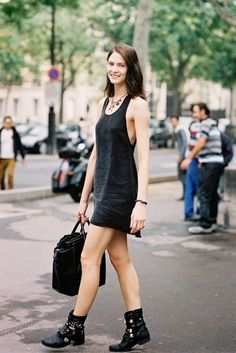 A black tank dress is worn with combat boots, a structured black tote and simple boho inspired jewelry.