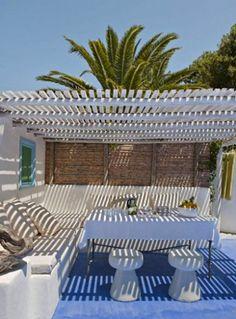Autre invitation à l'évasion avec cette sublime pergola créés par le designer Vera Yacha pour une maison grec. L'espace à l'abri du soleil est délimité au sol par une lumineuse peinture bleu azur qui s'arrête à l'aplomb du toit en tasseaux de bois peints en blanc. Les banquettes en ciment fabriquées sur place sont peintes en blanc cassé pour introduire le blond doré du mur en bois qui ferme le fond de la pergola.