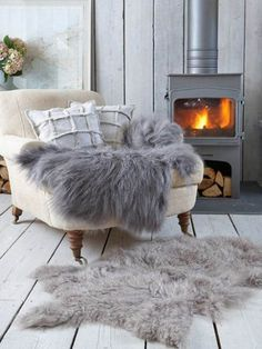 A stove fire with a cosy armchair, a fur throw blanket and a fur rug on the floor.