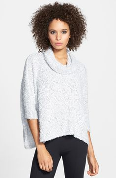 A drapey turtleneck and a swingy cropped hemline define a short-sleeve sweater cut in a boxy silhouette.