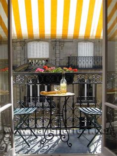 A cute, typically Parisian iron apartment balcony, with a brightly colored striped awning and romantic seating for two. Naturally, being in Paris, the table is laid with wine and a crusty baguette. :)