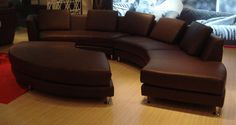 Curved Espresso Leather Sectional Sofa at www.GoWFB.ca | Multiple configurations! Transitional sectional sofa to suit contemporary living room standards. Espresso upholstery is made from high quality leather material that resists the constant wear and tear of every day living. This sofa includes a detachable ottoman piece that can be adjusted; allowing you to turn this modern sofa into a U or S-shaped seating area. Pillows incld. #Furniture #Canada | Free Shipping