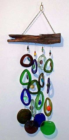 This unique Eco friendly gift will sing a toast to you with every breeze.    This beautiful Natural Beauty Wind chime consists of recycled wine bottles of green, clear, blue, amber and brown sliced and melted down to form 12 circular glass drops. The drops are accented with multi colored glass beads and anchored with 4 melted wine bottle bottom discs. The glass is suspended with woven nylon line from a natural driftwood top.