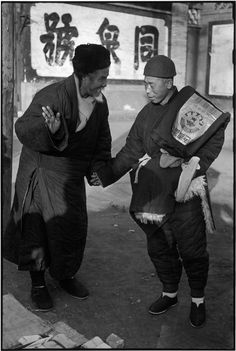 Henri Cartier-Bresson CHINA. Beijing. December 1948. A merchant and a client greet each other. No anxiety mars their cordial meeting although the city is besieged by troops of the People's Liberation Army. The Kuomintang was to flee within eight days. But even on the eve of such a dramatic event, the citizens retain the calm so typical of Beijing.