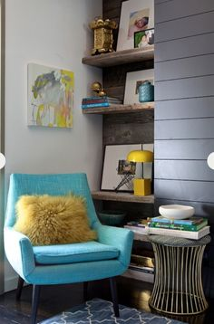 Driftwood shelving, turquoise and mustard palette, and a great modern chair.