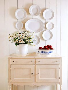 This cottage has a welcoming entrance. An antique buffet, dressed up with crystal knobs and lightly distressed ivory paint, welcomes guests and offers subtle tone-on-tone contrast in the cottage's crisp white entry. Farmhouse Decor, Decor, Plates Diy, Cottage Style Decor, Plates On Wall, Country Farmhouse Decor, Cottage Style, Home Decor, Decor Styles