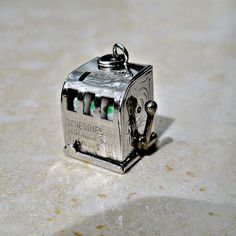 Vintage sterling silver one arm bandit slot machine movable charm from 1960s.  Articulated charm. 9/16 inch high, 1/2 inch wide, 1/2 deep.