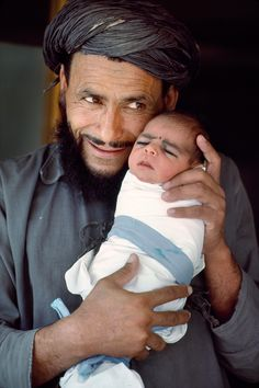 Proud Papa!  (The tiny baby already wears the traditional black eye liner of that region and culture -- Afghanistan?)