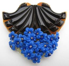 Gorgeous vintage carved black & gold Bakelite dress or fur clip with dangling blue celluloid flowers.
