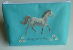 Pretty turquoise colour with a beautiful grey pony and the words 'Happy Go Lucky'  Made from durable canvas feel polyester the outside can be scrubbed clean.  The inside is lined, has a pocket, and can be wiped clean too.  Horse washbag measures 24cm x 17cm x 8cm. A perfect Horse gift.  http://flyingfetlocks.com.au/products/Happy_Go_Lucky_Washbag-79-51.html