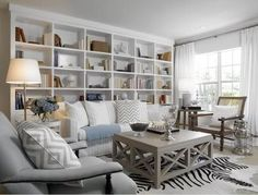 Neutral family room. Love the wall of shelving/display space in the background, the zebra rug and the rustic coffee table. Very cozy.