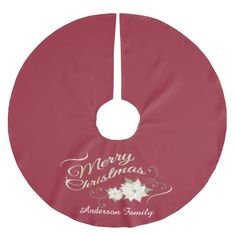 This Christmas tree skirt features a vintage inspired design of white poinsettias, green swirls and gold text: Merry Christmas. Personalize this red tree skirt with your family name.