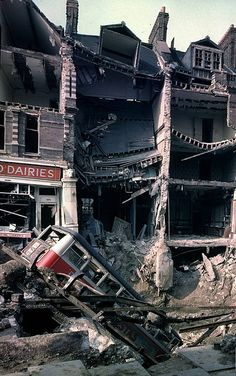 15 October 1940    Wreckage of bus leaning into huge crater in front of bombed out buildings, a result of German aerial blitz attacks during the Battle of Britain. (William Vandivert)