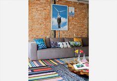 Na ampla sala de estar, o painel de madeira cumaru sobe do chão à parede. A tubulação exposta dá contraste imediato. O cinza ganha pitadas de energia com tons de vermelho em estampas das almofadas e no patchwork do tapete da Carbono Design. Reforma da arquiteta Andréia Reis