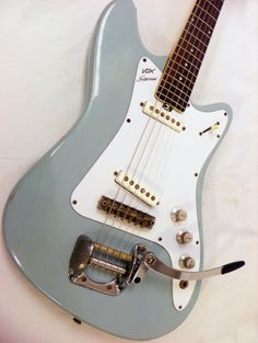 """This super cool vintage Vox Hurricane sports a nicely faded blue finish with dual single coil pickups and the distinctive """"rounded shark fin"""" headstock shape. These fine representatives of the 1960s were manufactured in Italy by the Eko Corporation likely between 1965 and 1968. It features a unique bridge assembly that is similar to a Bigsby style vibrato system, only with a little more give and response than most Bigsbys. The pickguard is a modern reproduction; ..."""