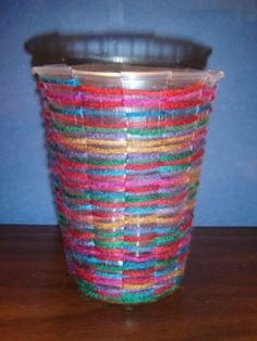Weaving with kids using a plastic disposable cup. Use as a bean planter.