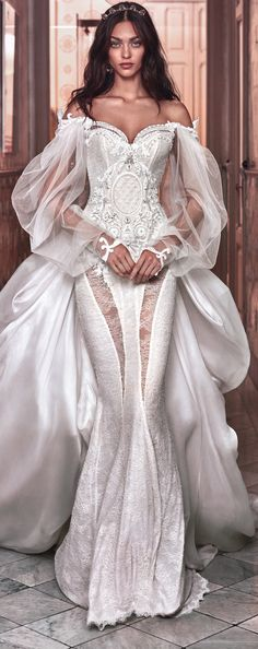 A Victorian wedding gown, homage to Queen Victoria's wedding gown, corseted with a sheer back made of a very delicate blush colored chantilly lace over a shimmery background. It has many sheer cut-outs, which accentuates the figure. The top has an elaborate vintage applique ornament which forms an off-the-shoulder neckline and has a sheer drape silk tulle sleeves. The appliques are decorated with multiple Swarovski crystals and pearls.