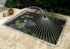 a bespoke abstract design child safety pond cover made from polished stainless steel