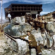 """The crew of an M4A1 Sherman tank mounted with an M8 """"Calliope"""" multiple rocket launcher read mail somewhere at some time between 1942 and 1945. ----------"""